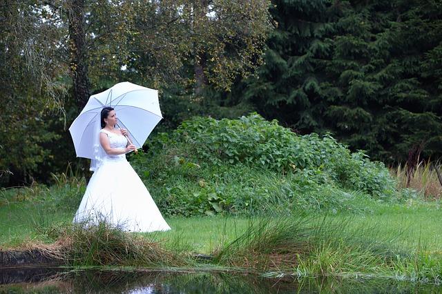 nevěsta, která se prochází s bílým deštníkem a závojem kolem rybníka v přírodě